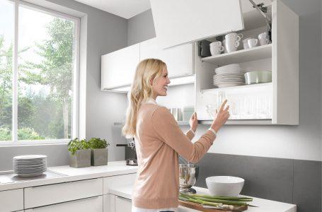 Frau stellt ein Glas in einen Hochschrank, der sich automatisch öffnet